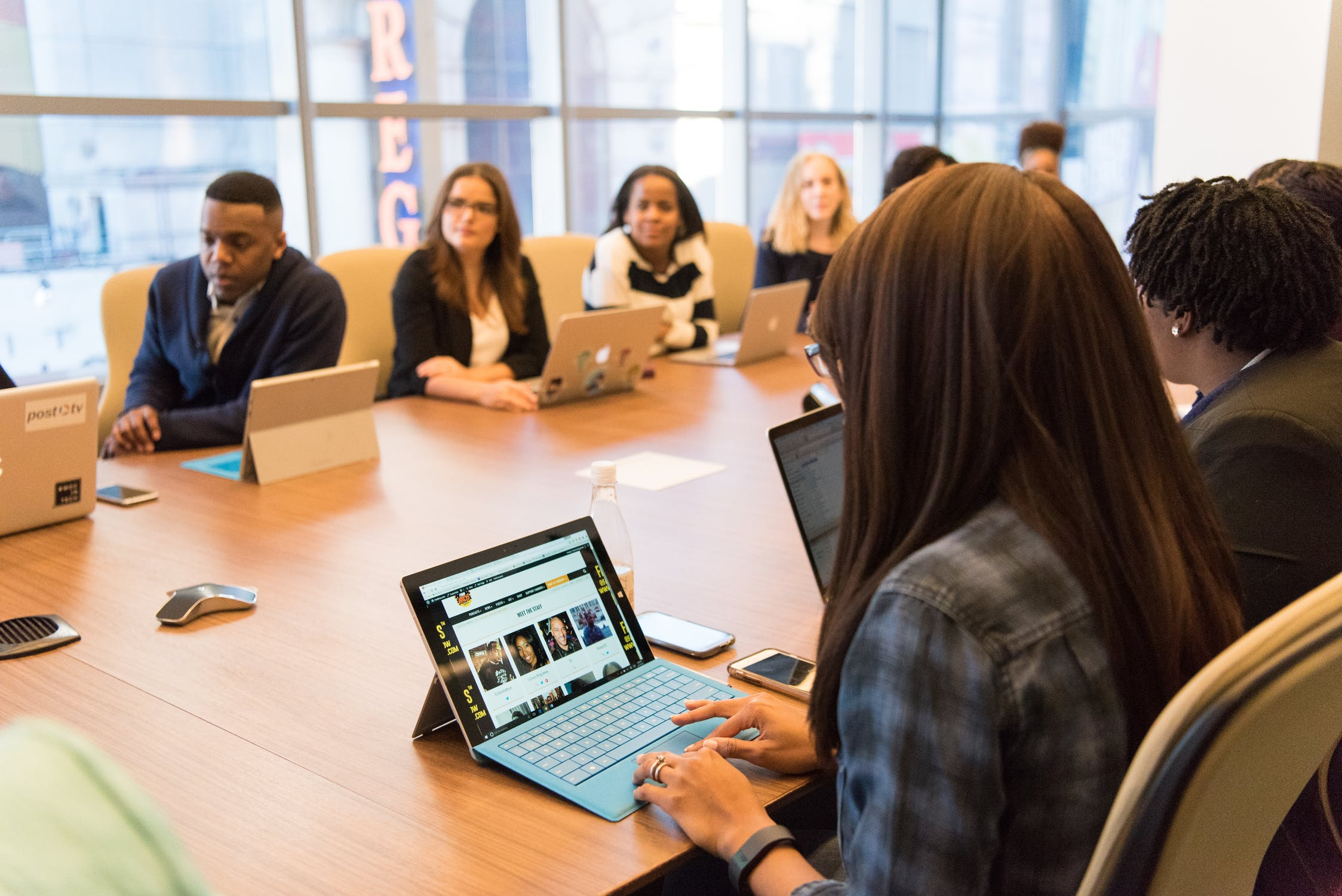 employees with laptops conference table