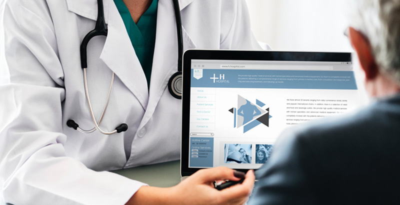Doctor showing a patient medical information on a laptop. Avoid costly fines with HIPAA/HITECH compliance.