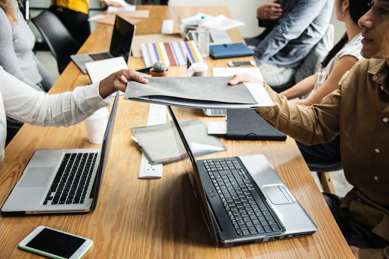 A group of workers meeting at a table with the two front most workers passing a folder between one another. This image emphasizes the importance of reaching goals as a team.
